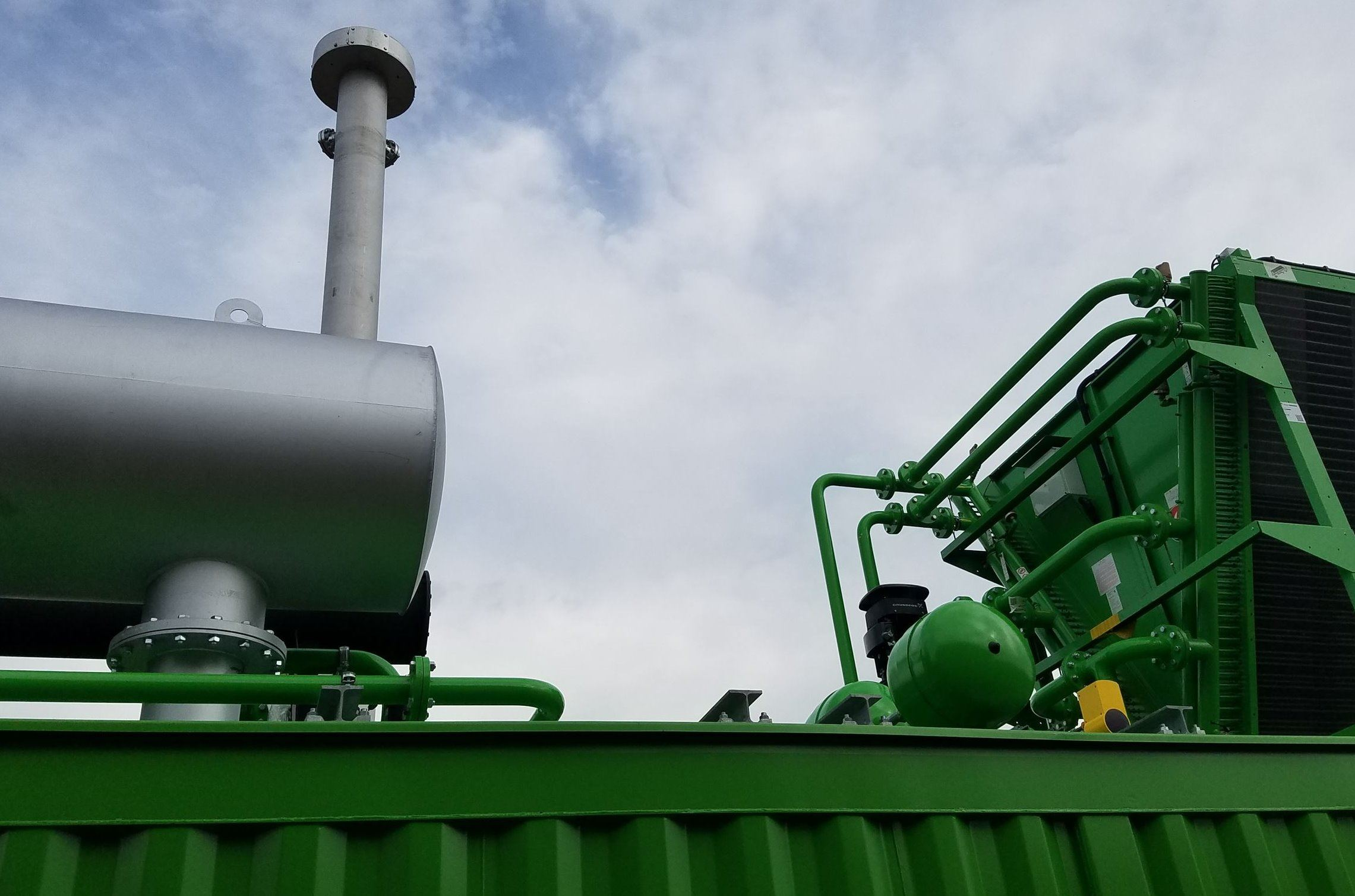 Green Generator Equipment outside with blue sky and clouds in background