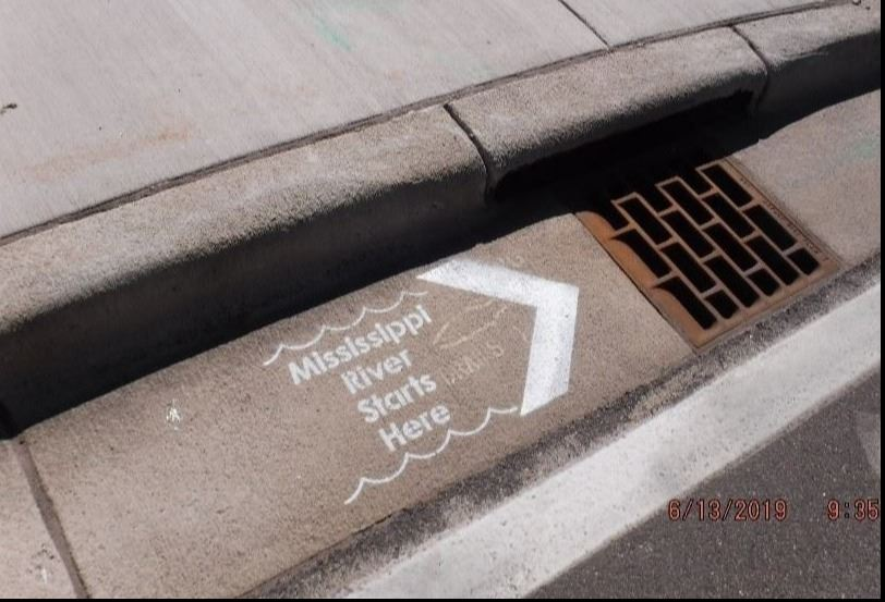 Curb and stormdrain with stencil marking
