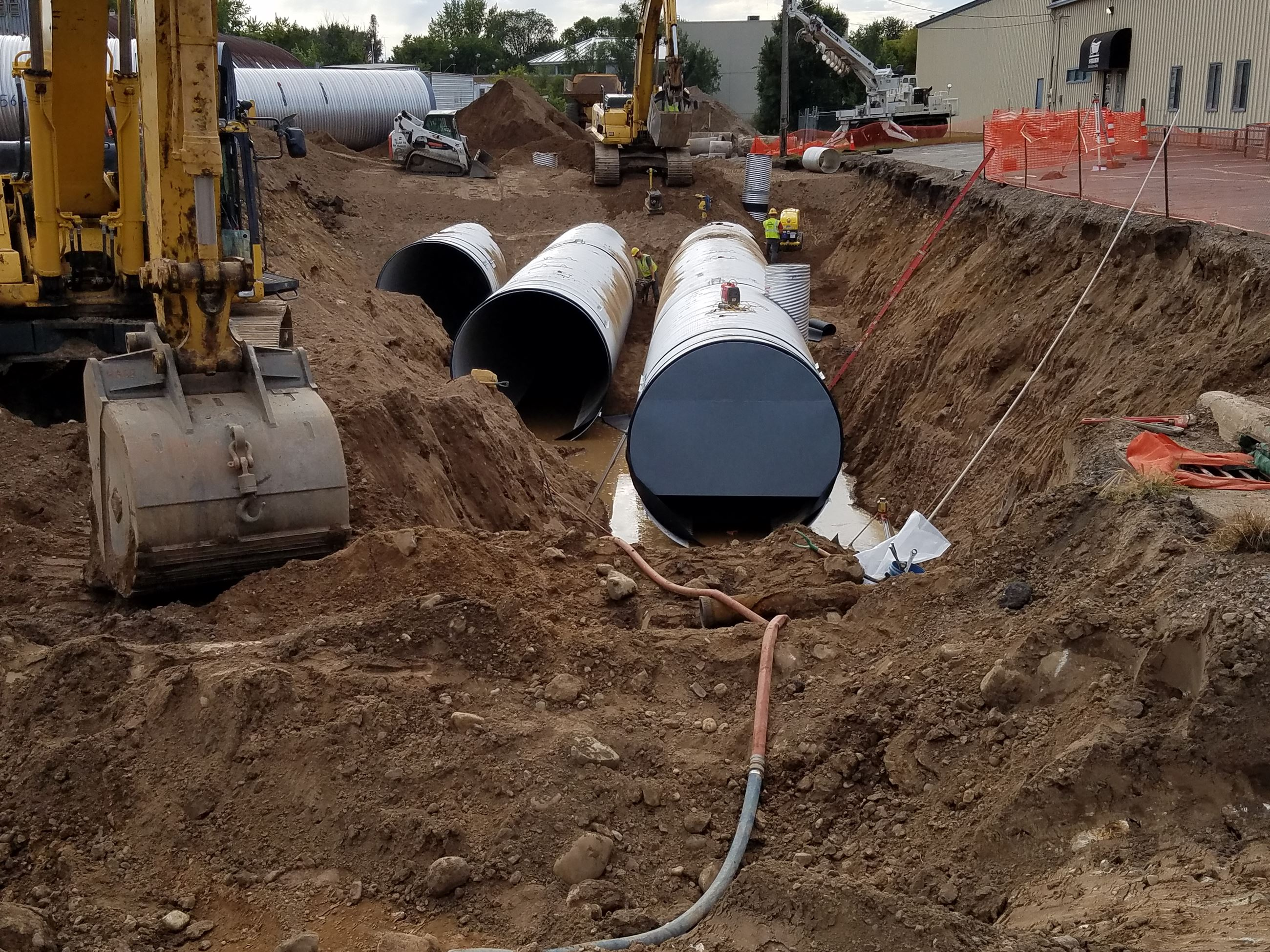 Large metal pipes and construction equipment resting in hole dug into ground
