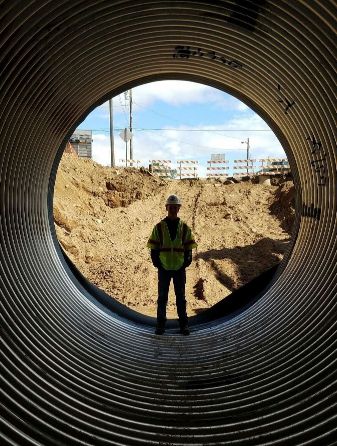 Person standing upright inside large empty pipe