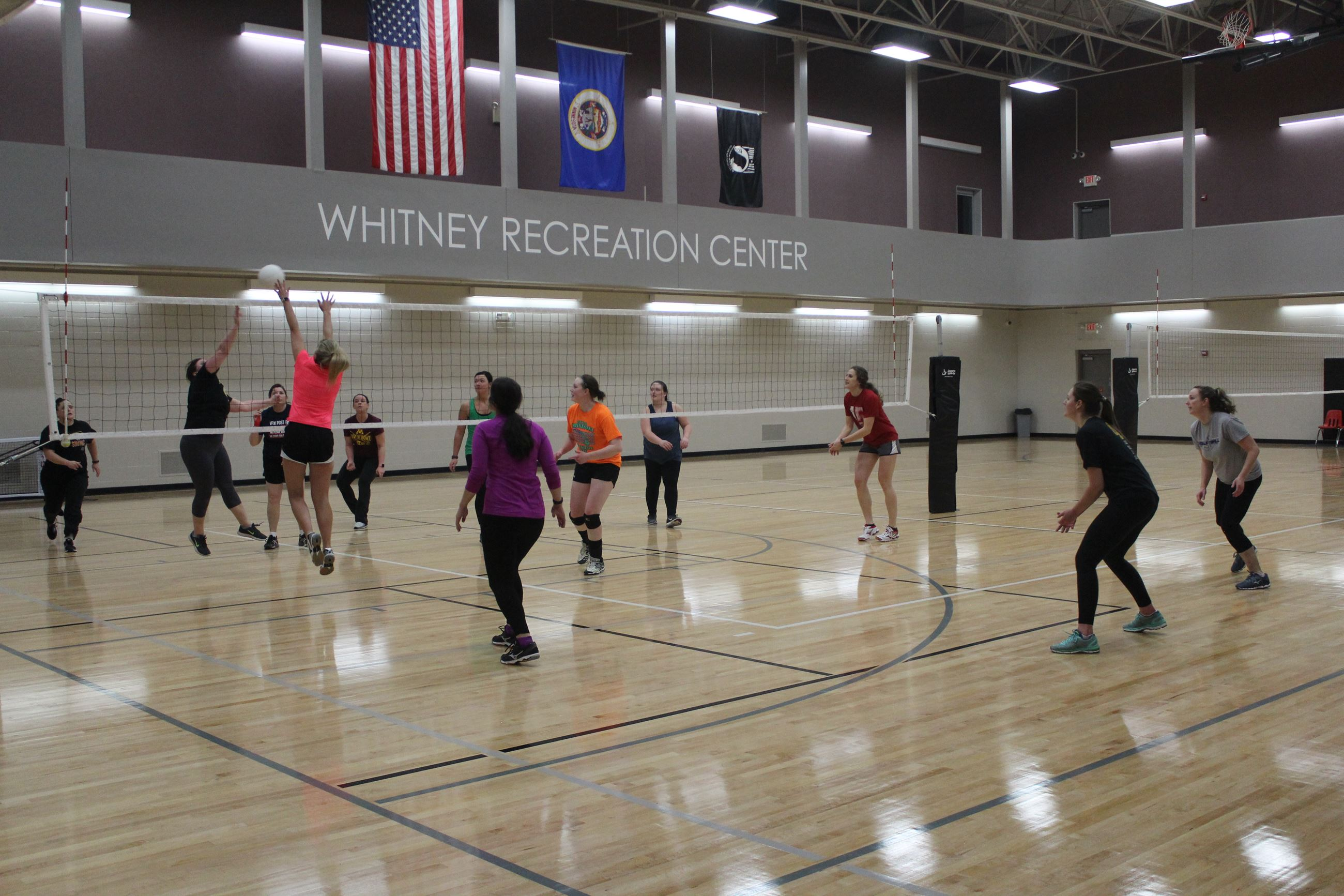 Volleyball game being played by two women's teams at the Whitney Recreation Center