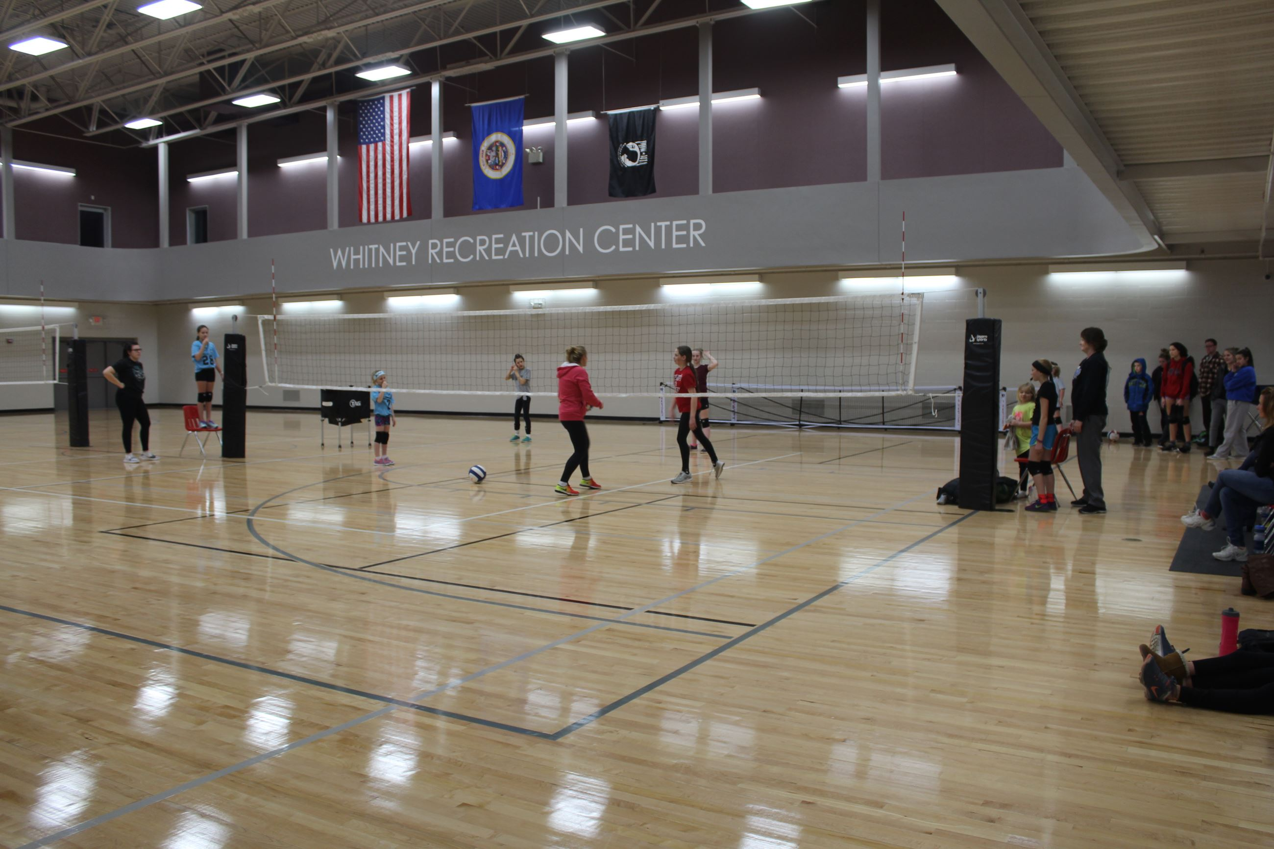 A group of girls receives instruction on playing the game of volleyball at the Whitney Recreation Ce