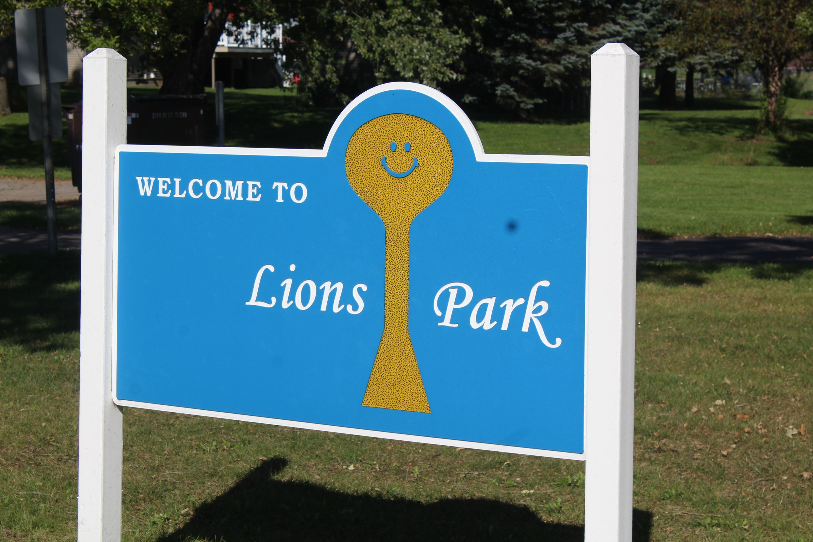 "Sign that reads ""Welcome to Lions Park"" and boasts a likeness of the Waite Park yellow smiling"