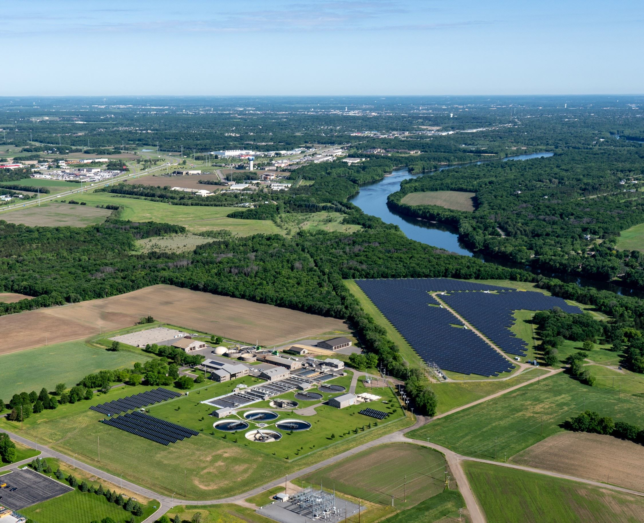Aerial view of buildings, water treatment ponds, solar panels, equipment, surrounding fields, river